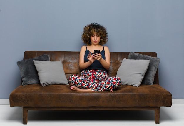 Jovens bonitas mulher em casa, com um telefone celular, de pijama no sofá