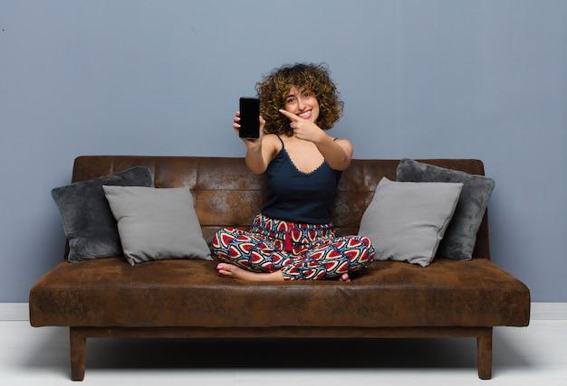 Jovens bonitas mulher em casa, com um telefone celular, vestindo pijamas em um sofá