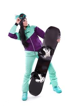 Jovens bonitas mulher em traje de esqui roxo segurar snowboard