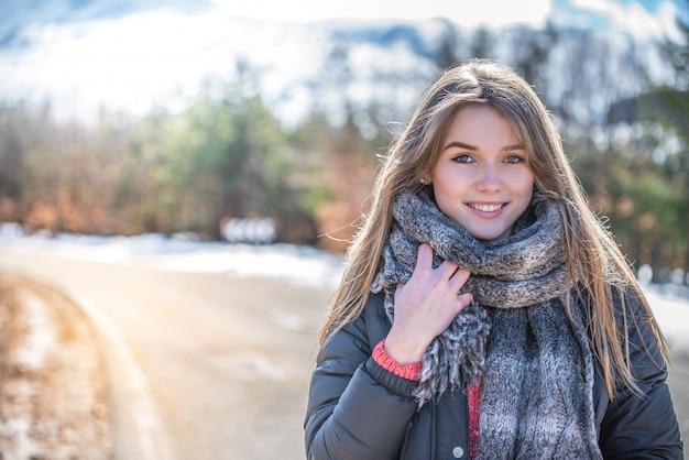 Jovens bonitas mulher em uma estrada com neve no inverno