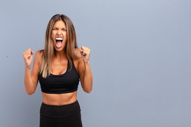 Jovens bonitas mulher gritando agressivamente com uma expressão de raiva ou com os punhos cerrados comemorando o sucesso