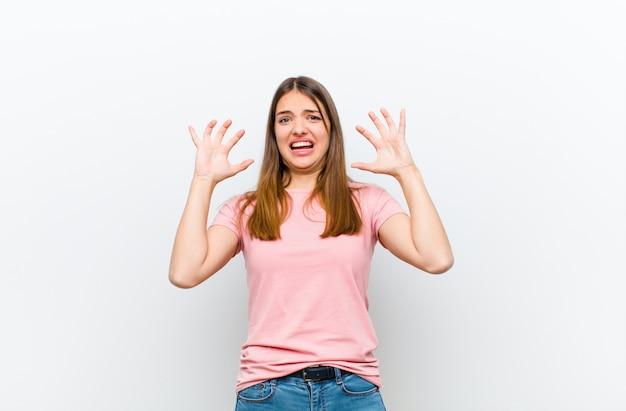 Jovens bonitas mulher gritando com as mãos no ar, sentindo-se furioso, frustrado, estressado e chateado contra a parede branca