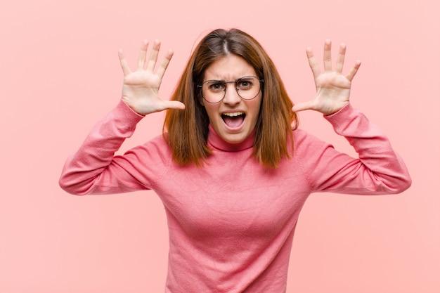 Jovens bonitas mulher gritando de pânico ou raiva, chocado, aterrorizado ou furioso, com as mãos ao lado da cabeça contra a parede rosa