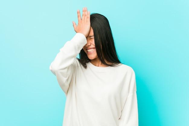 Jovens bonitas mulher hispânica esquecendo algo, batendo na testa com a palma da mão e fechando os olhos.