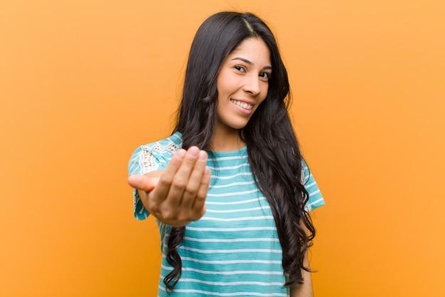 Jovens bonitas mulher hispânica, sentindo-se feliz, bem-sucedida e confiante, enfrentando um desafio e dizendo: traga-o! ou recebê-lo contra a parede marrom