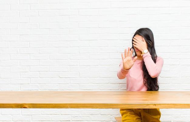 Jovens bonitas mulher latina, cobrindo o rosto com a mão e colocando a outra mão na frente para parar a câmera, recusando fotos sentado em frente a uma mesa