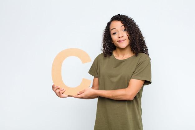 Jovens bonitas mulher latina confusa, duvidosa, pensando, segurando a letra c do alfabeto para formar uma palavra ou uma frase.
