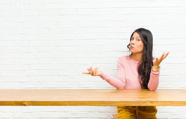 Jovens bonitas mulher latina, encolher os ombros com uma expressão idiota, louca, confusa e confusa, sentindo-se irritada e sem noção sentado em frente a uma mesa