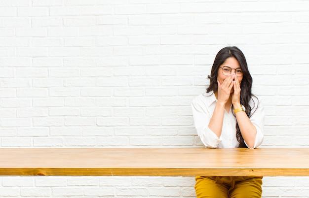 Jovens bonitas mulher latina olhando feliz, alegre, sortudo e surpreso cobrindo a boca com as duas mãos, sentado na frente de uma mesa