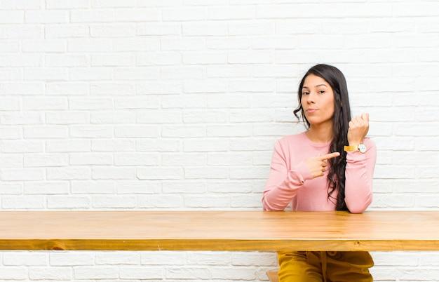 Jovens bonitas mulher latina olhando impaciente e com raiva, apontando para o relógio pedindo pontualidade quer chegar a tempo