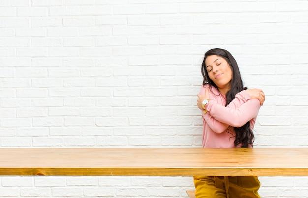 Jovens bonitas mulher latina se sentindo apaixonada, sorrindo, abraçando e abraçando a si mesma, ficando solteira, sendo egoísta e egocêntrica, sentada na frente de uma mesa