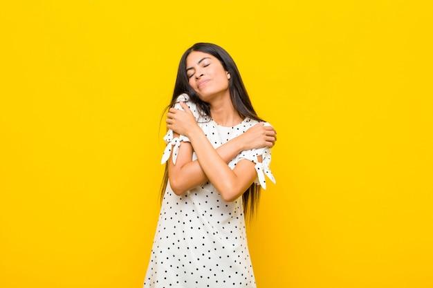 Jovens bonitas mulher latina se sentindo apaixonada, sorrindo, abraçando e abraçando a si mesma, permanecendo solteira, sendo egoísta e egocêntrica contra a parede plana
