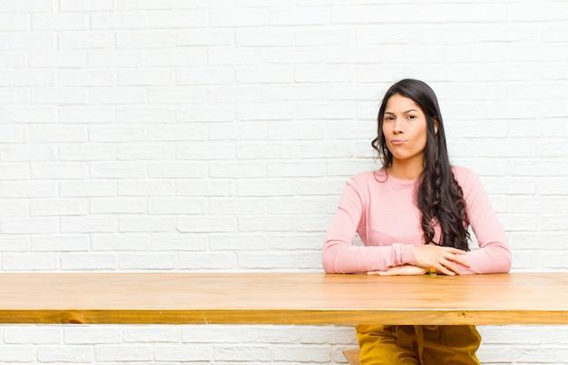 Jovens bonitas mulher latina se sentindo confusa e duvidosa, querendo saber ou tentando escolher ou tomar uma decisão sentado em frente a uma mesa