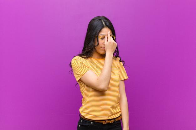 Jovens bonitas mulher latina sentindo estressado, infeliz e frustrado, tocando a testa e sofrendo de enxaqueca de dor de cabeça severa contra a parede roxa