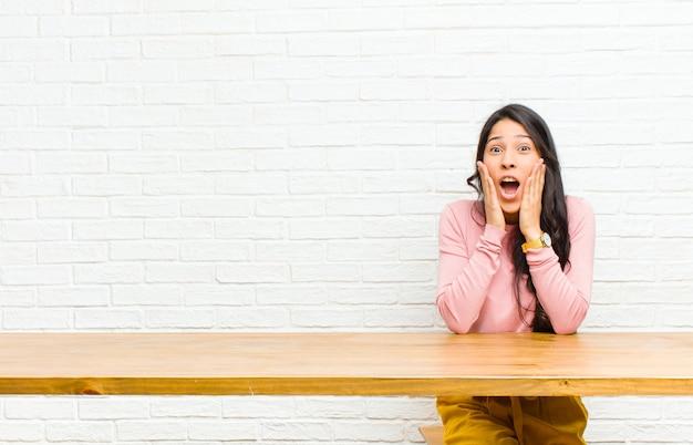 Jovens bonitas mulher latina, sentindo-se feliz, animado e surpreso, olhando para o lado com as duas mãos no rosto, sentado na frente de uma mesa