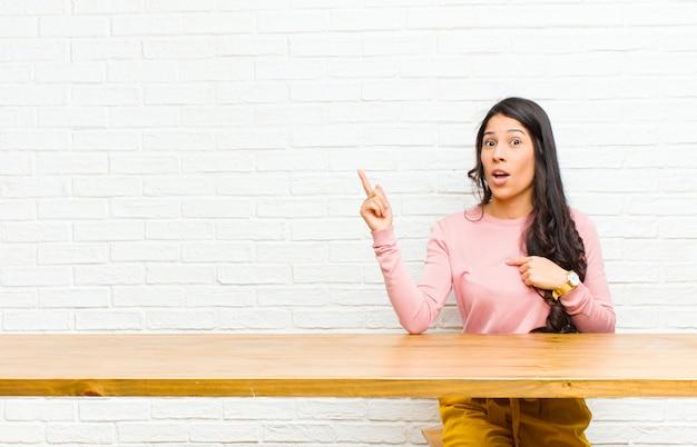 Jovens bonitas mulher latina, sentindo-se orgulhoso e surpreso, apontando para si mesmo com confiança, sentindo-se como o número um bem-sucedido sentado em frente a uma mesa
