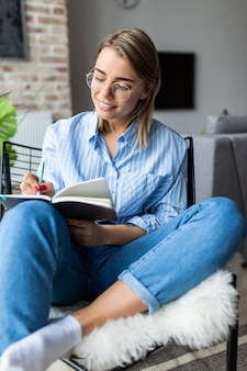 Jovens bonitas mulher lendo ou anotar um livro e sentado na cadeira confortável em casa