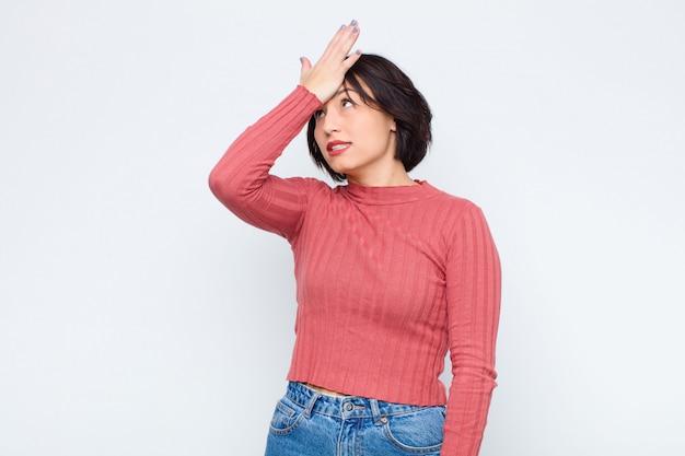 Jovens bonitas mulher levantando a palma da mão na testa pensando opa, depois de cometer um erro estúpido ou lembrar, sentindo-se burro contra a parede branca