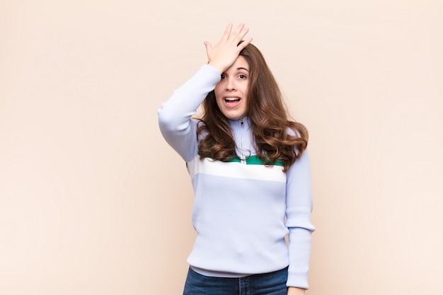 Jovens bonitas mulher levantando a palma da mão na testa pensando opa, depois de cometer um erro estúpido ou lembrar, sentindo-se burro contra parede bege