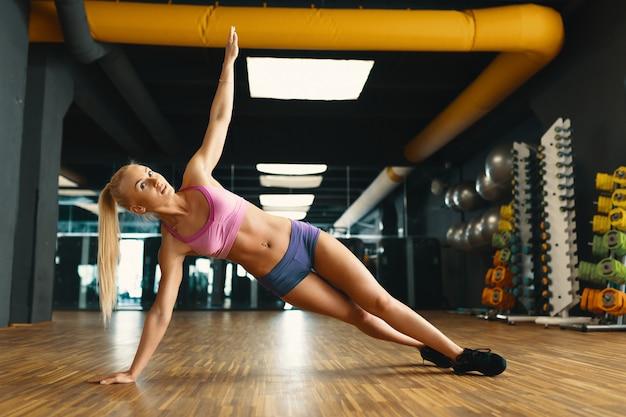 Jovens bonitas mulher malhando com peso pessoal em uma academia moderna