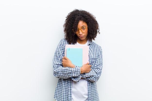 Jovens bonitas mulher negra com parede branca de livros