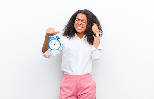 Jovens bonitas mulher negra com um despertador contra parede branca