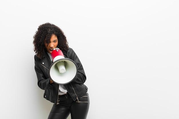 Jovens bonitas mulher negra com um megafone, vestindo uma jaqueta de couro contra parede branca