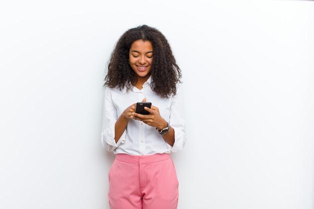 Jovens bonitas mulher negra com um telefone inteligente contra parede branca