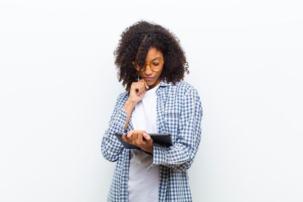 Jovens bonitas mulher negra com uma parede branca tablet inteligente