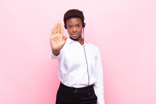 Jovens bonitas mulher negra olhando sério fazendo gesto de parada