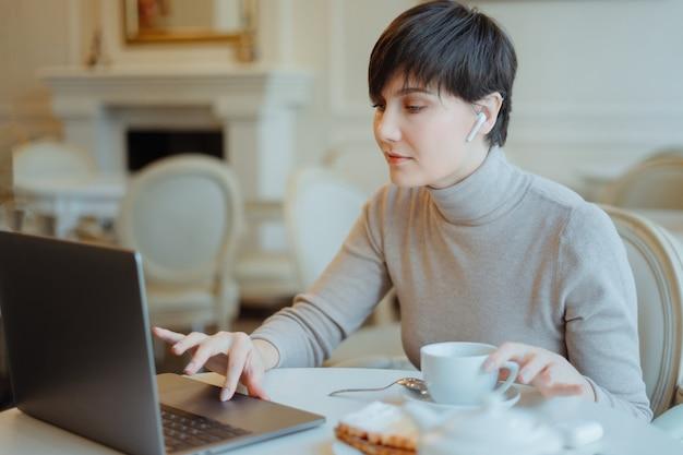 Jovens bonitas mulher no café com fones de ouvido, ouvindo música e trabalhando com o laptop