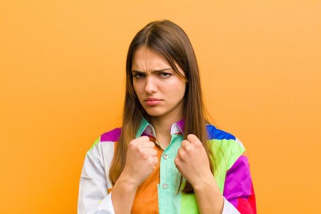 Jovens bonitas mulher olhando confiante, irritado, forte e agressivo, com os punhos prontos para lutar em posição de boxe por cima do muro