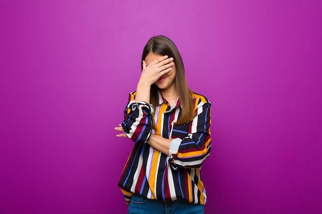Jovens bonitas mulher olhando estressado, envergonhado ou chateado, com dor de cabeça, cobrindo o rosto com a mão contra a parede roxa