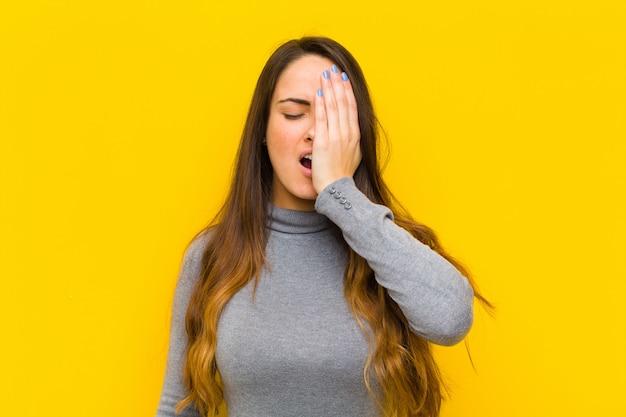 Jovens bonitas mulher olhando sonolento, entediado e bocejando, com uma dor de cabeça e uma mão cobrindo metade do rosto emprego ou conceito de negócio
