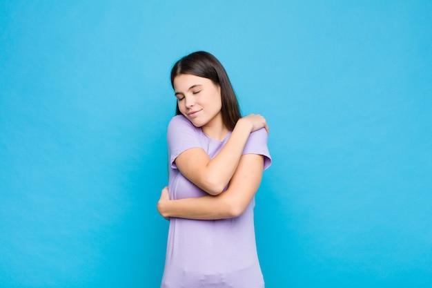 Jovens bonitas mulher se sentindo apaixonado, sorrindo, abraçando e abraçando a si mesmo, ficando solteiro, sendo egoísta e egocêntrico sobre parede azul