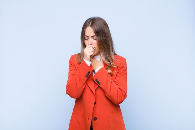 Jovens bonitas mulher se sentindo doente com sintomas de dor de garganta e gripe, tosse com a boca coberta por parede azul