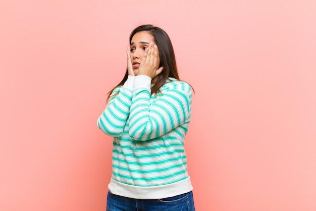 Jovens bonitas mulher se sentindo feliz, animado e surpreso, olhando para o lado com as duas mãos no rosto sobre parede rosa
