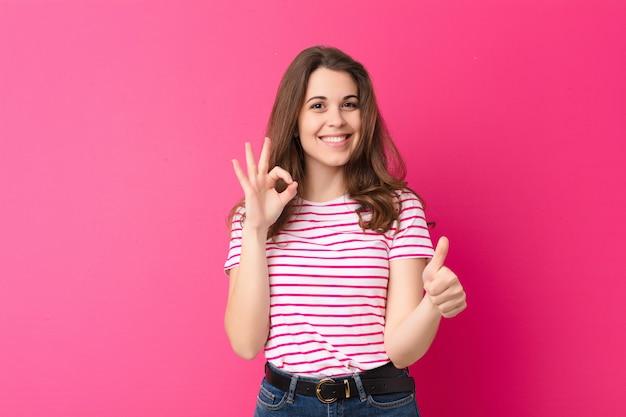 Jovens bonitas mulher se sentindo feliz, espantado, satisfeito e surpreso, mostrando bem e polegares para cima gestos, sorrindo contra parede rosa