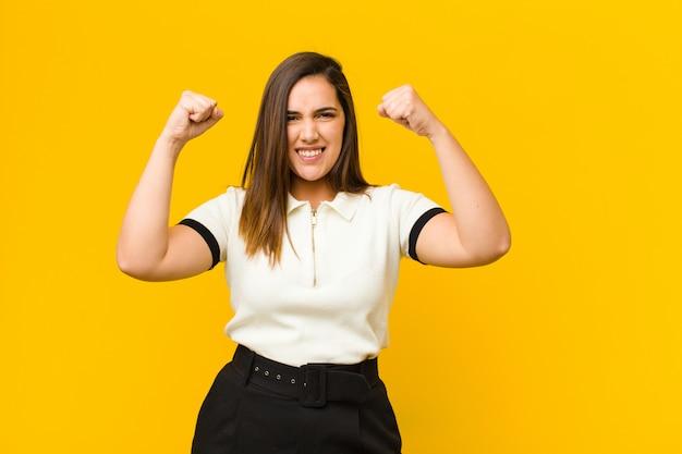 Jovens bonitas mulher se sentindo feliz, positiva e bem sucedida, comemorando a vitória