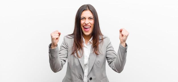 Jovens bonitas mulher se sentindo feliz, surpreso e orgulhoso, gritando e comemorando o sucesso com um grande sorriso isolado de parede branca