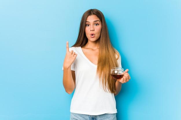 Jovens bonitas mulher segurando uma xícara de chá, tendo uma ótima idéia