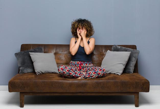 Jovens bonitas mulher sentindo medo ou vergonha, espreitar ou espiar com os olhos semicobertos com as mãos, sentado em um sofá.