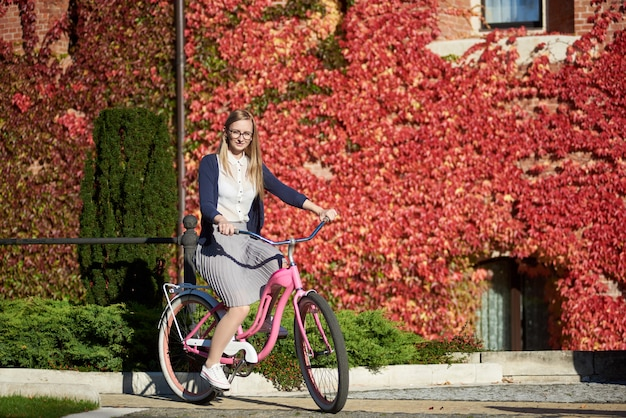 Jovens bonitas mulher sorridente, andar de bicicleta de senhora-de-rosa no dia ensolarado quente e brilhante na parede de tijolo