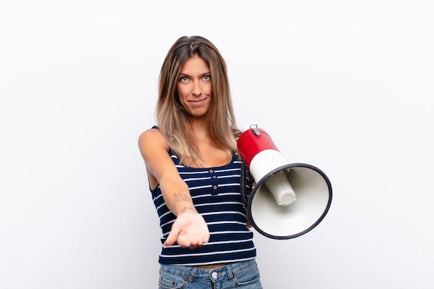 Jovens bonitas mulher sorrindo alegremente com olhar amigável, confiante e positivo, oferecendo e mostrando um objeto com um megafone