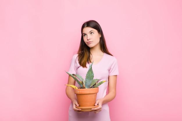 Jovens bonitas mulher sorrindo alegremente e sonhando acordado ou duvidando, olhando para o lado com uma planta