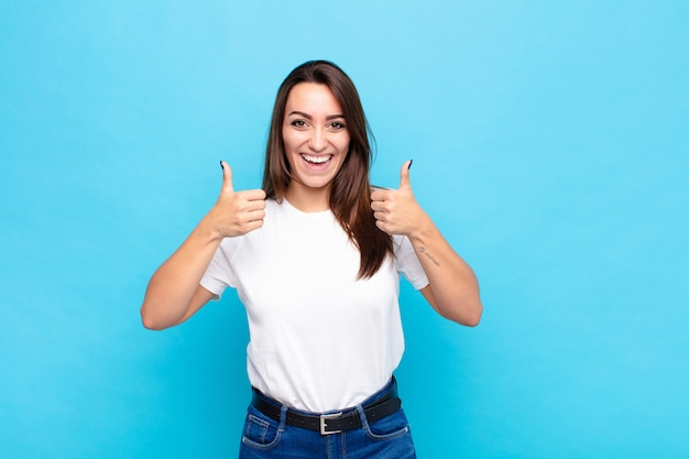 Jovens bonitas mulher sorrindo amplamente olhando feliz, positivo, confiante e bem sucedido, com os dois polegares para cima sobre parede azul