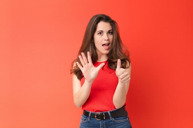 Jovens bonitas mulher sorrindo e olhando amigável, mostrando o número seis ou sexto com a mão para a frente, contando contra a parede vermelha
