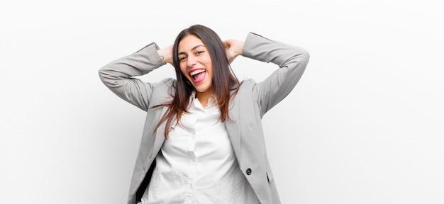 Jovens bonitas mulher sorrindo e se sentindo relaxado, satisfeito e despreocupado, rindo positivamente e relaxando a parede branca isolada