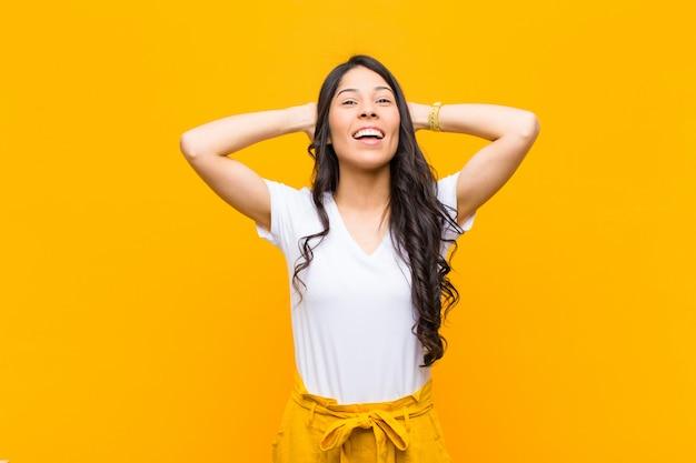 Jovens bonitas mulher sorrindo e se sentindo relaxado, satisfeito e despreocupado, rindo positivamente e relaxando na parede laranja