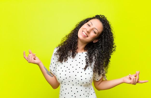 Jovens bonitas mulher sorrindo, sentindo-se despreocupado, relaxado e feliz, dançando e ouvindo música, se divertindo em uma festa ao longo da parede de chroma key
